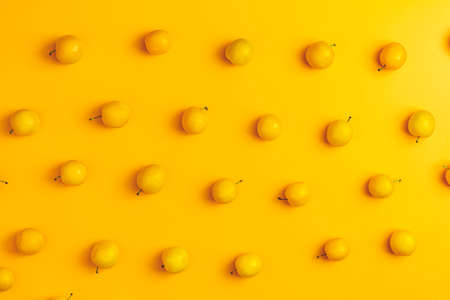 Creative summer pattern made of fresh yellow cherry plums on pastel yellow background. Fruit minimal concept. Flat lay.