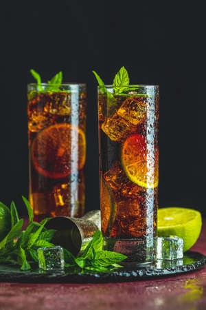 Cold Longdrink Cuba Libre with brown rum and fresh lime in highball glass with water drops on dark background, selective focus Stock Photo - 129770843