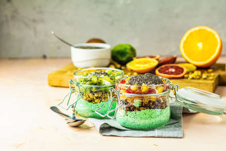 Two chia seed pudding with matcha green tea, kiwi and granola, orange in glasses on light pink concrete background. Healthy breakfast. Stock Photo - 129770966