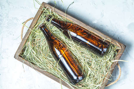 Craft beer with dried grass in wooden box on gray concrete surface background Stock Photo - 129771394