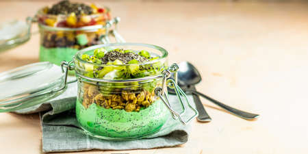 Two chia seed pudding with matcha green tea, kiwi and granola, orange in glasses on light pink concrete background. Healthy breakfast. Image banner format Stock Photo - 129771589
