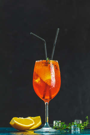 Aperitif cocktail in big wine glass with water drops on dark background. Summer alcohol cocktail with orange slices. Stock Photo - 130483474