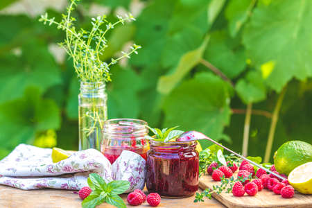 Raspberry jam and fresh raspberry on a rustic wooden table outdoors. Sunny day, green leaves background Stock Photo - 130483783
