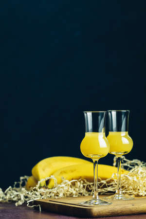 Banana flavoured liqueurs, which French call creme de banana, in  grappas wineglass on dark concrete surface. European aperitif drink. Selective focus, shallow depth of the fields, copy space. Stock Photo - 130483796