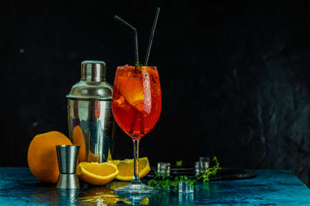 Aperitif cocktail in big wine glass with water drops on dark background. Summer alcohol cocktail with orange slices.  Trendy beverage Stock Photo - 130483868