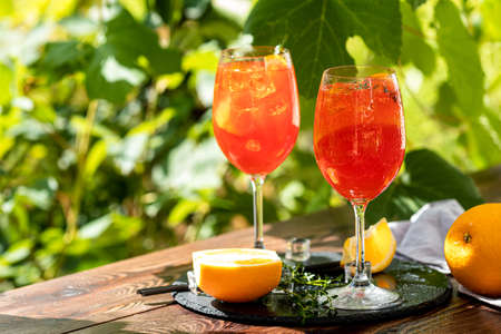 Two aperitif cocktail in big wine glass with oranges, summer Italian fresh alcohol cold drink. Sunny garden with vineyard background, summer mood concept, selective focus Stock Photo - 130483962