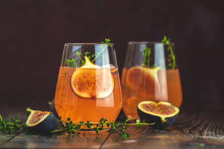 Pink cocktail with fig, thyme and ice in glass on dark wooden background, close up. Summer drinks and alcoholic cocktails. Alcoholic or detox cocktail Stock Photo - 130484263