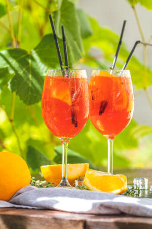 Two aperitif cocktail in big wine glass with oranges, summer Italian fresh alcohol cold drink. Sunny garden with vineyard background, summer mood concept, selective focus Stock Photo - 130485374