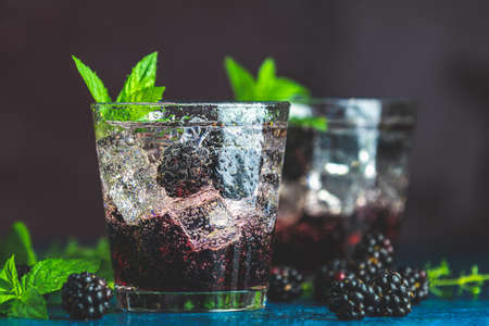 Cold summer berry drink with blackberries. Refreshing summer drink with syrup, blackberry and ice on dark blue concrete background Stock Photo - 130485468