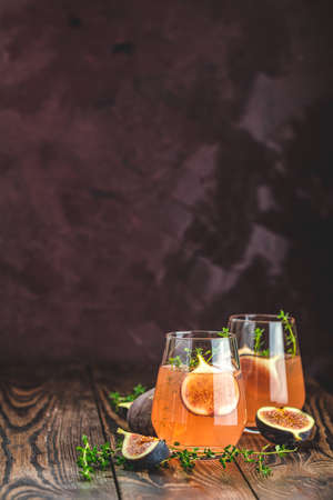 Pink cocktail with fig, thyme and ice in glass on dark wooden background, close up. Summer drinks and alcoholic cocktails. Alcoholic or detox cocktail Stock Photo - 130485950
