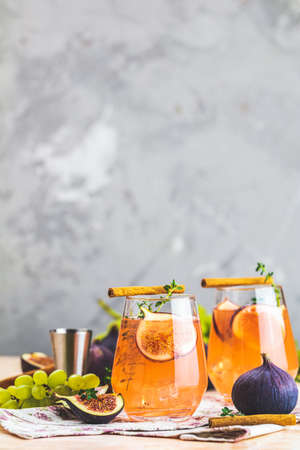 Pink cocktail with fig, thyme, cinnamon and grapes in glass on pink concrete background, close up. Autumn drinks and alcoholic cocktails. Alcoholic cocktail or detox drink Stock Photo - 130485992