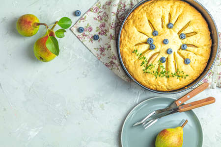 Delicious dessert blueberry tart with fresh berries and pears, sweet tasty cheesecake, berry pie on gray concrete surface table. French cuisine. Flat lay, top view, copy space for text Stock Photo - 130485662
