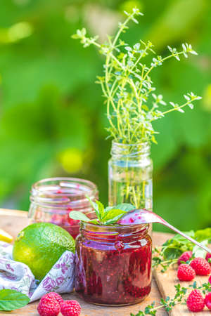Raspberry jam and fresh raspberry on a rustic wooden table outdoors. Sunny day, green leaves background Stock Photo - 130485827