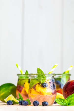 Blueberry and peach infused water, cocktail, lemonade or tea in jar with water drops. Summer iced cold drink with blueberry, lime, peach and mint Stok Fotoğraf