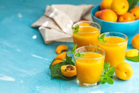 Glass of fresh healthy apricot or peach smoothie or juice on light blue concrete surface table. Sunny light. Shallow depth of the field, close up, copy space for you text