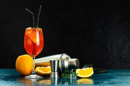 Cocktail  in big wine glass with water drops on dark background. Summer alcohol cocktail with orange slices.