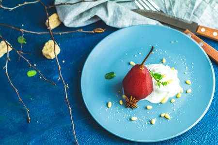 Pears in wine. Traditional dessert pears stewed in red wine with chocolate sauce on plate on blue concrete surface. Concept for romantic dinner dessert. Simple Paleo style dessert pear
