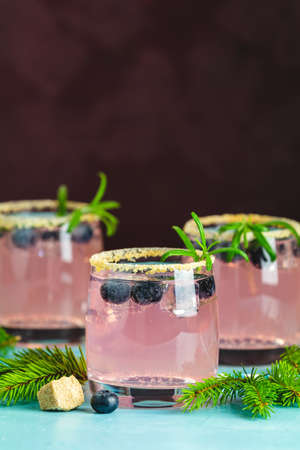 Fresh blueberry cocktail with rosemary and ice in glasses with decorate brown sugar on turquoise surface and black background. Christmas and New Year holiday welcome drink Zdjęcie Seryjne