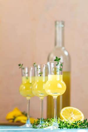 Limoncello with thyme in grappas wineglass with water drops on light concrete table. Artistic still life on light background with sunny light.