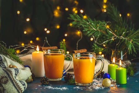 Christmas and New Year composition. Two cup of hot spicy tea with sea buckthorn, cinnamon and star anise, branches of pine and spruce, candles and holiday decor, bokeh, dark background 写真素材