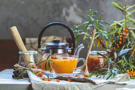 Cup and teapot of hot spicy tea with sea buckthorn, jam in the glass jar, branches of fresh berries on light woden table surface in the rustic room 写真素材 - 132822912