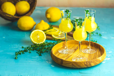 Limoncello with thyme in three grappas wineglass in wooden tray, fresh lemon in basket on light concrete table. Artistic still life on light background. Zdjęcie Seryjne