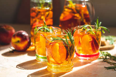 Glasses with drops of sweet peach iced tea, Summer cold peach fizz cocktail with rosemary. Sunny light. Shallow depth of the field, close up, copy space for you text