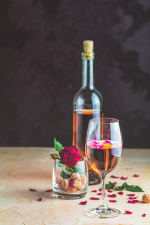 Bottle of rose wine and glass served with rose wine and rose petals, rose and candied fruit in glass on pink concrete table and dark background. Beautiful valentine or wedding greeting card.