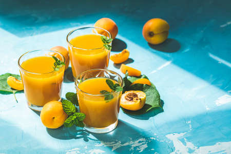 Glass of fresh healthy apricot or peach smoothie or juice on light blue concrete surface table. Sunny light. Shallow depth of the field, close up, copy space for you text 写真素材 - 132822925