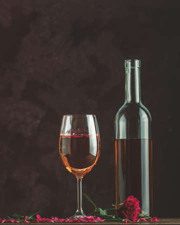 Bottle of rose wine and glass served with rose wine and rose petals, pink rose on dark background. Beautiul valentine or wedding greeting card.