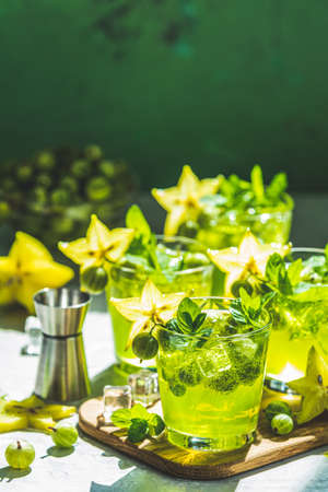 Green gooseberry and carambola cocktail with liqueur, ice and fresh mint on a light gray concrete table. Refreshing summer drink, sunny light. Or detox drink Zdjęcie Seryjne