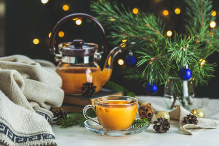 Christmas and New Year composition. Cup and teapot of hot spicy tea with sea buckthorn, jam in the glass jar, branches of pine and spruce, holiday decor, bokeh, dark background