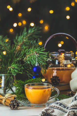 Christmas and New Year composition. Cup and teapot of hot spicy tea with sea buckthorn, jam in the glass jar, branches of pine and spruce, holiday decor, bokeh, dark background 写真素材 - 132822928