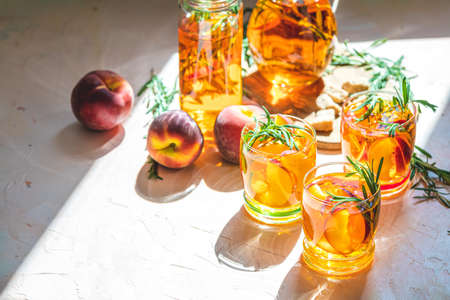 Glasses of sweet peach iced tea, Summer cold peach fizz cocktail with rosemary. Sunny light. Shallow depth of the field, close up, copy space for you text