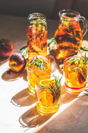 Glasses of sweet peach iced tea, Summer cold peach fizz cocktail with rosemary. Sunny light. Shallow depth of the field, close up, copy space for you text 写真素材 - 132822937