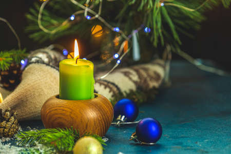 Christmas and New Year composition. Candles and holiday decor, branches of pine and spruce,  bokeh, dark background.