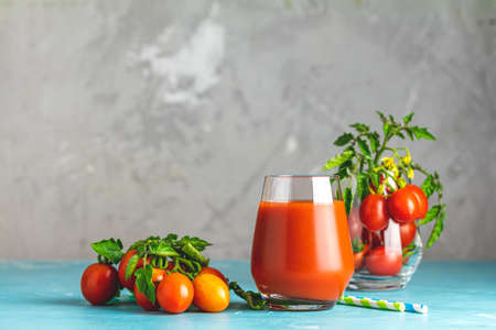 Glass of fresh delicious jummy red tomato juice and fresh tomatoes on light concrete surface. Close up. Gmo free. Natural good food. Stok Fotoğraf - 131320790