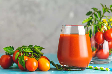 Glass of fresh delicious jummy red tomato juice and fresh tomatoes on light concrete surface. Close up. Gmo free. Natural good food.