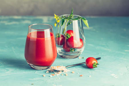 Glasses of fresh delicious red tomato juice and fresh raw tomatoes with pink salt in spoon on light concrete surface. Close up. Gmo free. Natural good food. 写真素材 - 132823591