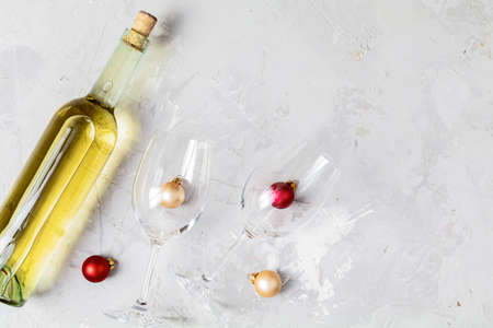 Creative food art background. Bottle of wine and two wine glasses with red and gold сhristmas balls on light gray concrete surface, top view, flat lay, copy space for you text.