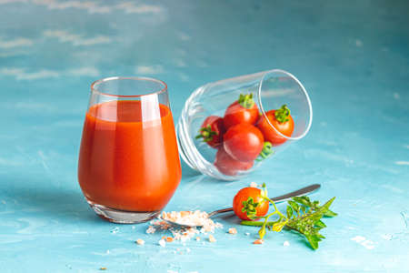 Glasses of fresh delicious jummy red tomato juice and fresh raw tomatoes with pink salt in spoon on light concrete surface. Close up. Gmo free. Natural good food. Stok Fotoğraf