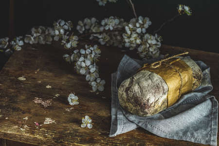 Freshly baked rye handmade breads on old wooden table with linen napkin and apricot tree blossom branch. Dark rustic style. Photo styling of paintings by Flemish painters 写真素材 - 132823522
