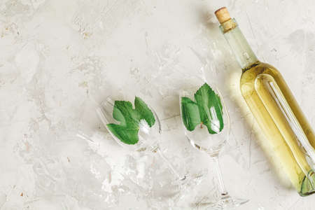 Creative food art background. Bottle of wine and two wineglasses with green grape leaves on light gray concrete surface, top view, flat lay, copy space for you text.