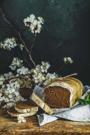 Freshly baked rye handmade breads on old wooden table with linen napkin and apricot tree blossom branch. Dark rustic style. Photo styling of paintings by Flemish painters