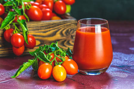 Glass of fresh delicious jummy red tomato juice and fresh tomatoes in wooden box. Dark background. Close up. Gmo free. Natural good food Stok Fotoğraf - 131315819