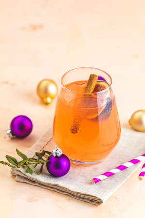 Christmas and New Year pink cocktail with fig and cinnamon  in glass on pink concrete background, close up, surrounded  holiday decor. Winter festive drinks and alcoholic cocktails or detox drink Imagens