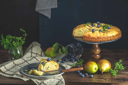 Delicious dessert blueberry tart with fresh berries and pears, sweet tasty cheesecake, berry pie. French cuisine Artistic Still Life in the style of Dutch painting. Copy space for you text Standard-Bild