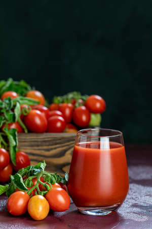 Glass of fresh delicious jummy red tomato juice and fresh tomatoes in wooden box. Dark background. Close up. Gmo free. Natural good food Stok Fotoğraf