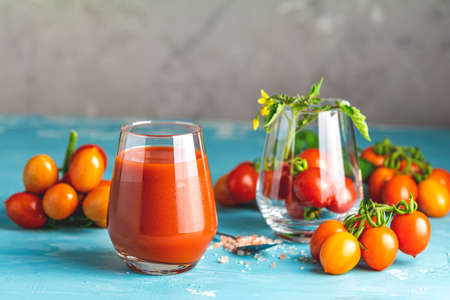 Glasses of fresh delicious jummy red tomato juice and fresh raw tomatoes with pink salt in spoon on light concrete surface. Close up. Gmo free. Natural good food. Stok Fotoğraf - 131315412