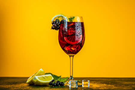 Cold red cocktail with blackcurrant, lemon, mint and ice in tall glass on yellow background. Summer drinks and alcoholic cocktails. Alcoholic cocktail Blackcurrant mojito